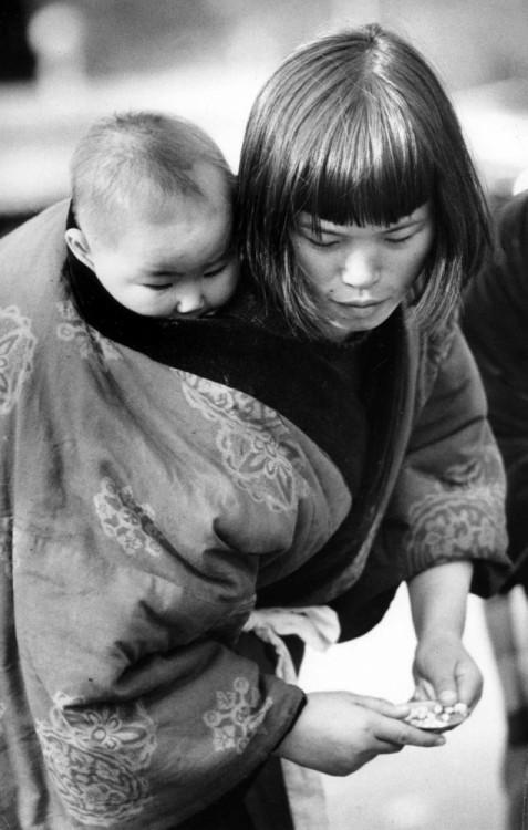 madre japonesa con su hijo en la espalda