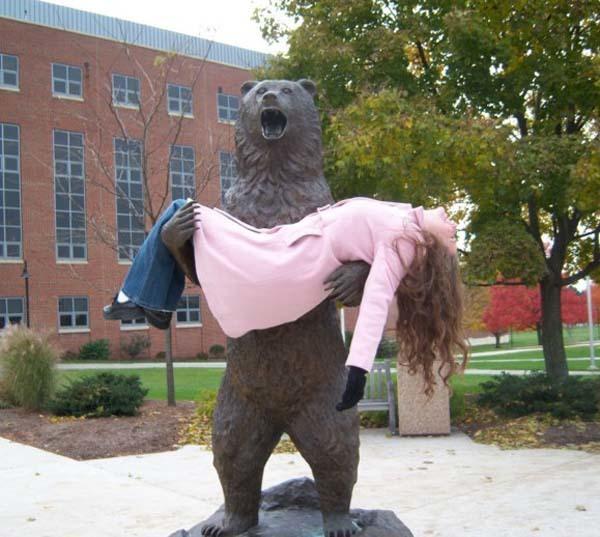 mujer en brazo de estatua de oso