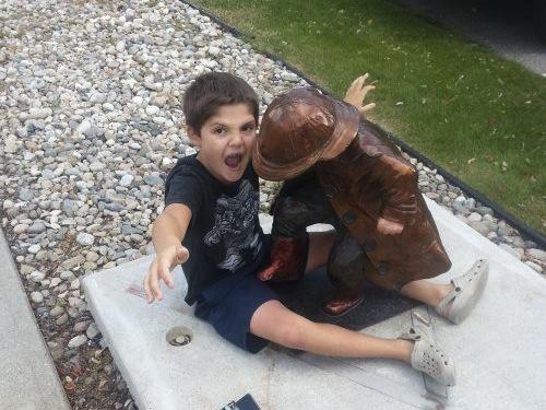 niño jugando con estatua