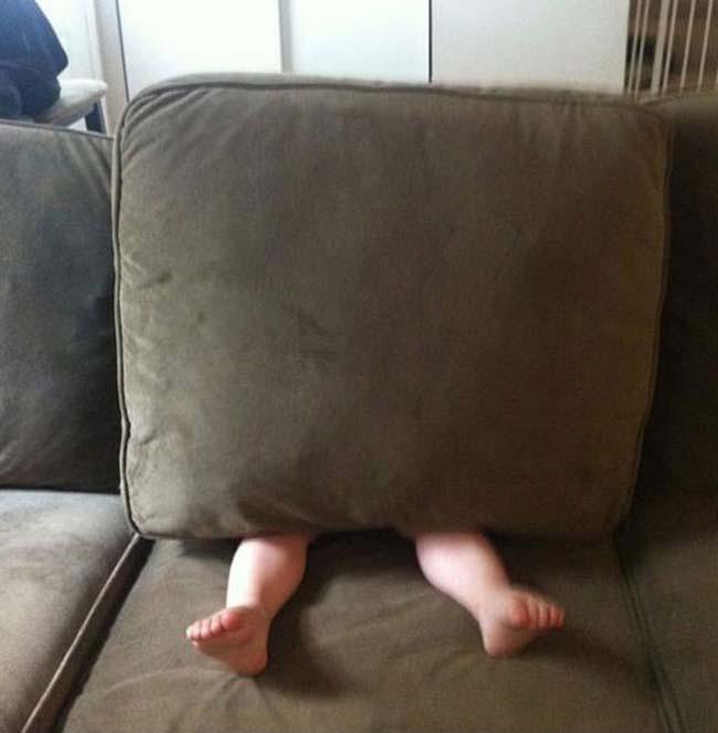 niño escondiéndose debajo del sillon