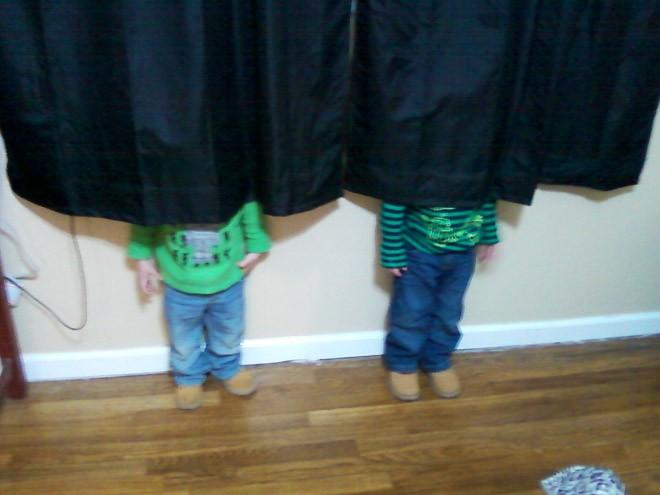 niños escondiéndose detrás de una cortina