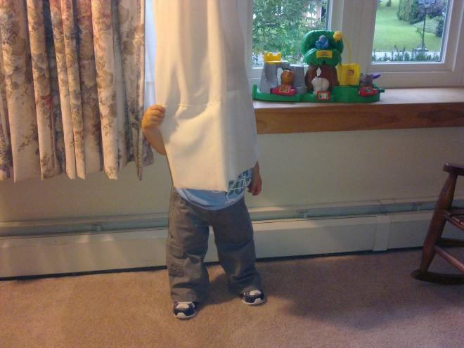 niño escondiéndose detrás de una cortina