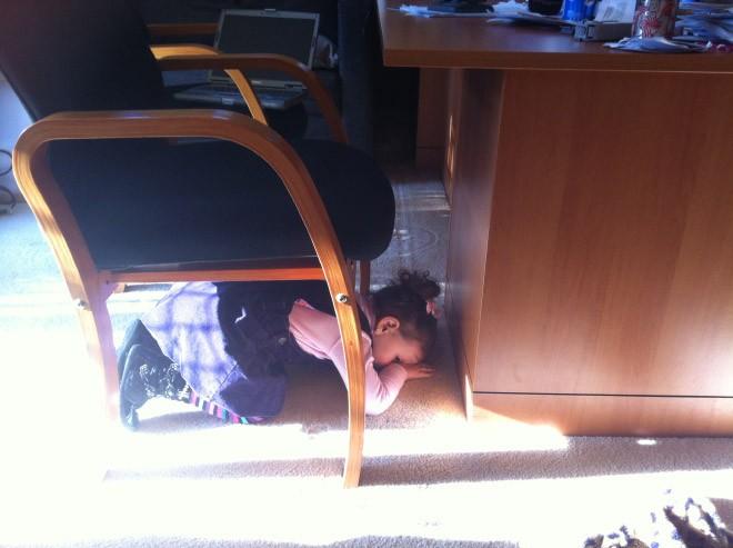 niño escondiéndose debajo del escritorio