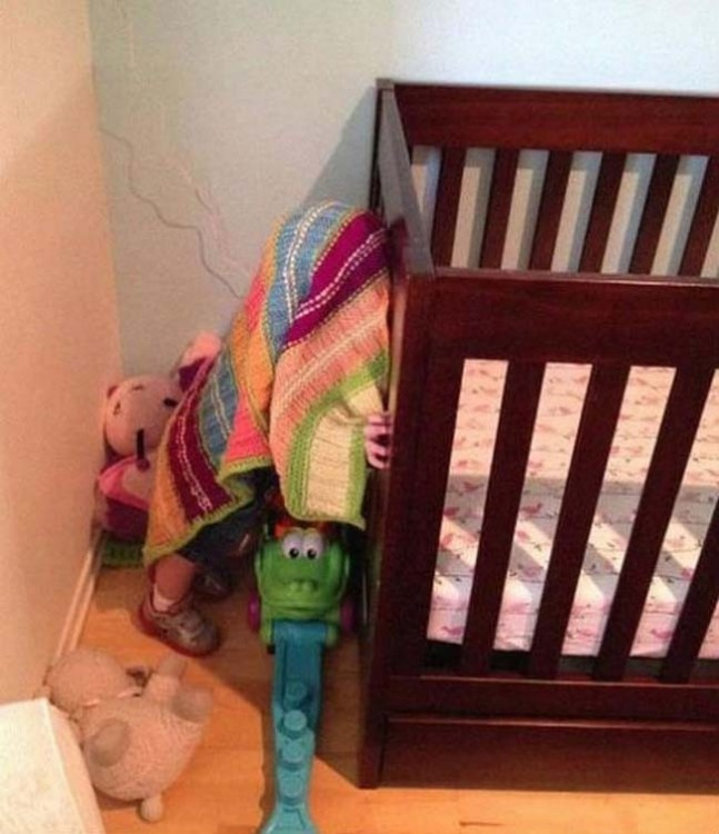 niño escondiéndose debajo de una toalla
