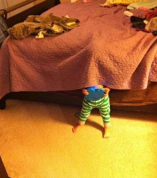 niño escondiéndose debajo de la sabana