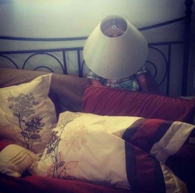 niño escondiéndose detrás de la lampara