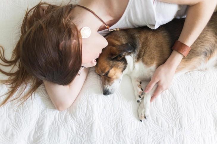 mujer y perro durmiendo en la cama