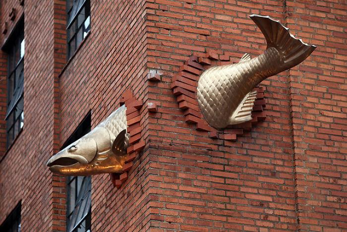 Salmón incrustado en una pared, arte urbano