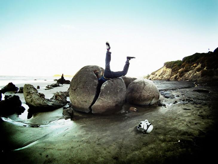 hombre metido en media roca circular de una playa muy fria