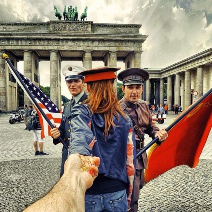 Dos actores con uniformes de soldados posan con Natalia en la Puerta de Brandemburgo de Berlín.