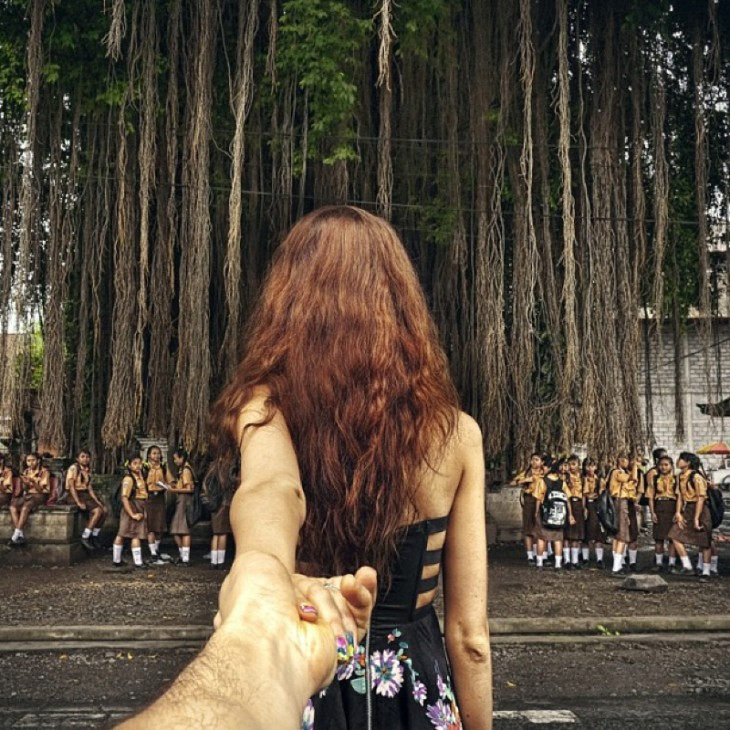 Niñas de la escuela plantean bajo un gran árbol con las uvas que cuelgan