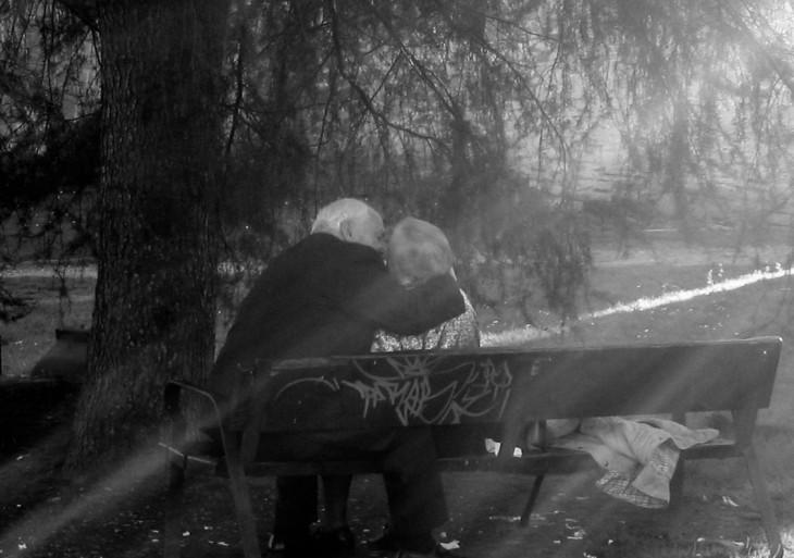 ancianos besandose en una banca