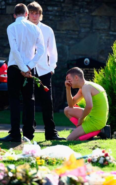 chico con vestido hincado en el suelo llorando en el funeral de su mejor amigo