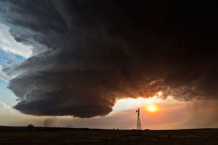 Paisaje con una enorme nube en forma de remolino y a lado el sol ocultándose