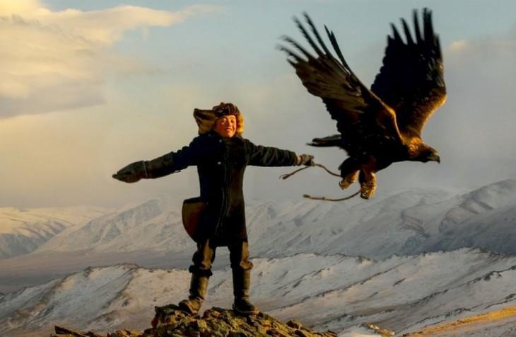 Niño arriba de una montaña junto a un águila volando en Mongolia