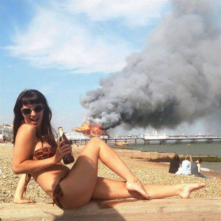 Fotogfrafía de una chica en traje de baño mientras detrás de ella un barco se quema