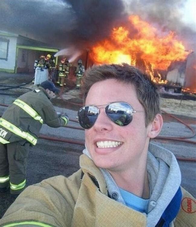 Selfie de un chico que detrás tiene un incendio