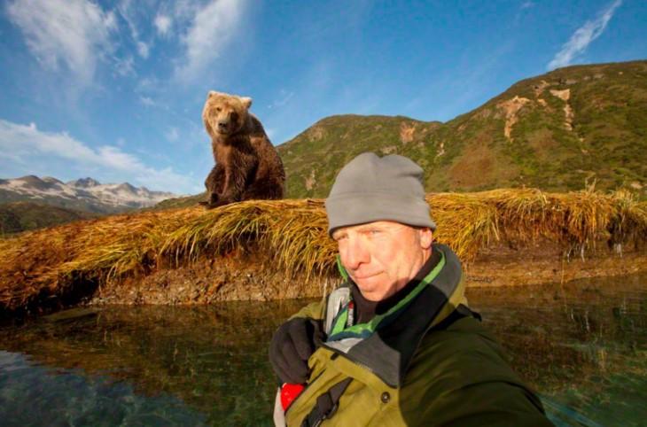 Hombre tomándose una Selfie en un lago con un osos detrás de él