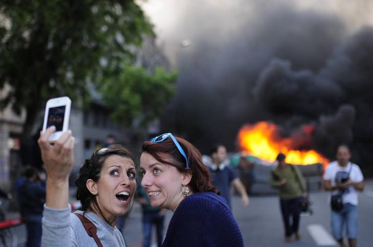 Selfie de dos chicas durante una explosión detrás de ellas