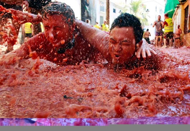 Fiesta de la tomatina, personas nadan en tomates en españa