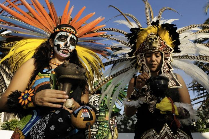 Personas disfrazadas de indigenas Aztecas, celebran el día de los muertos