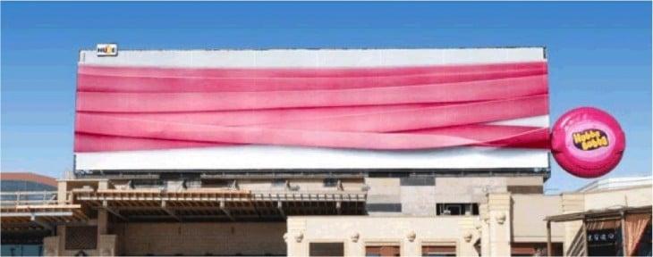 goma rosada envuelve edificio en publicidad de goma de mascar