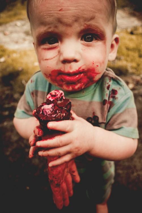 un pequeño niño disfrazado de Zombie simulando que se esta comiendo una mano
