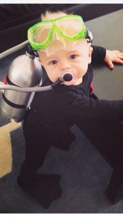 un bebé disfrazado de buzo parado frente a una mesa