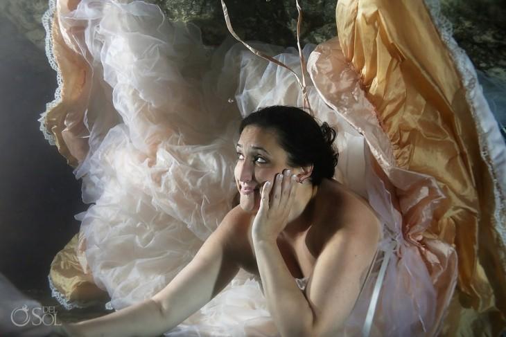 mujer vestida de novia debajo del mar con una mano en la cara