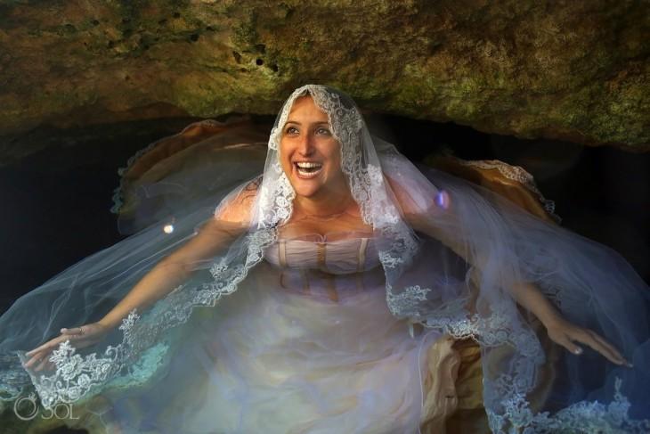 Mujer vestida de novia dentro del agua sonriendo y mirando hacia arriba