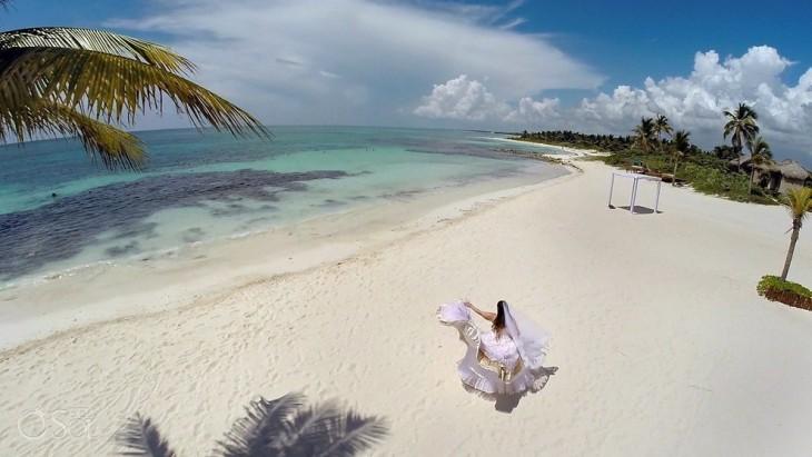 Chica vestida de novia a la orilla de una playa