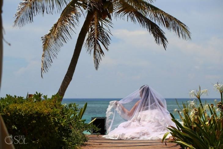Chica sentada a la orilla de una playa con un portaretratos a un lado