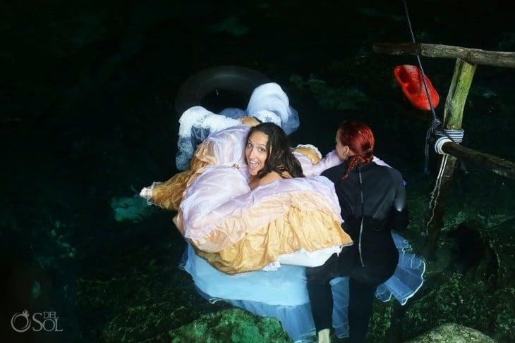 Chica dentro de mar vestida de novia con una mujer a un costado