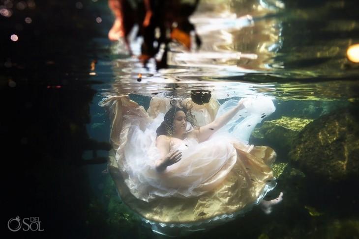 Chica vestida de novia sumergida en el agua entre rocas