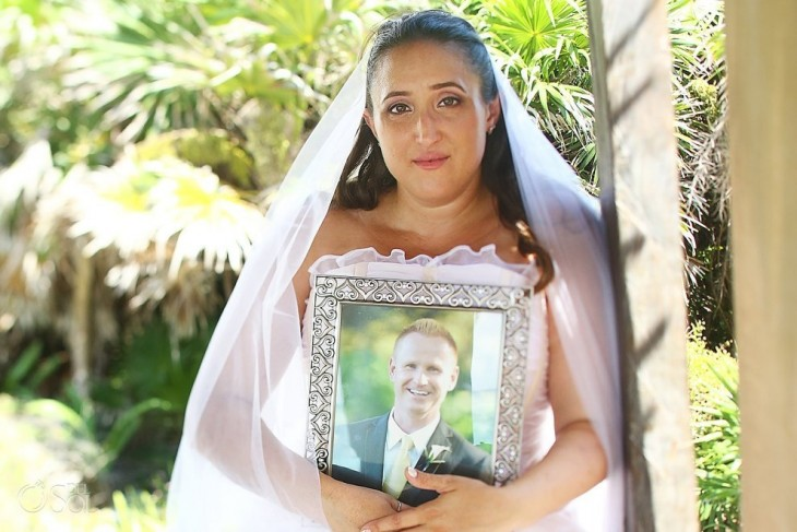 Mujer vestida de novia con la foto de su prometido recargada en su pecho
