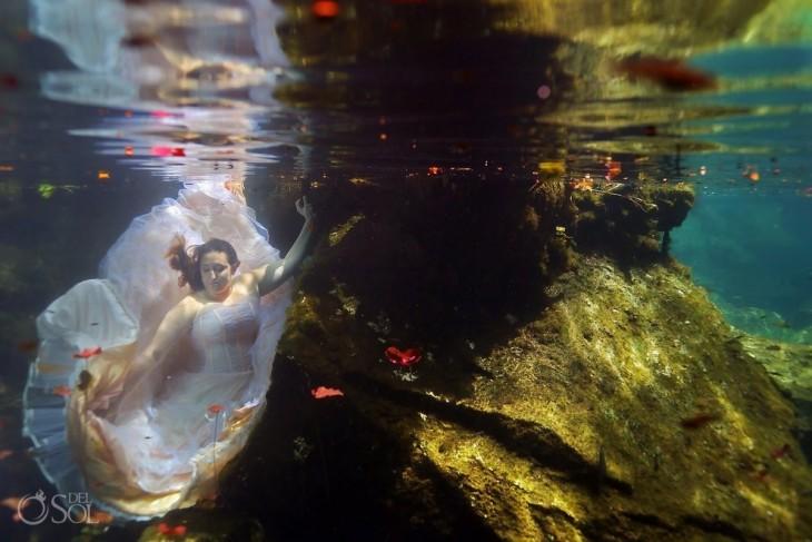 una mujer vestida de novia posando debajo del mar sosteniéndose de una piedra