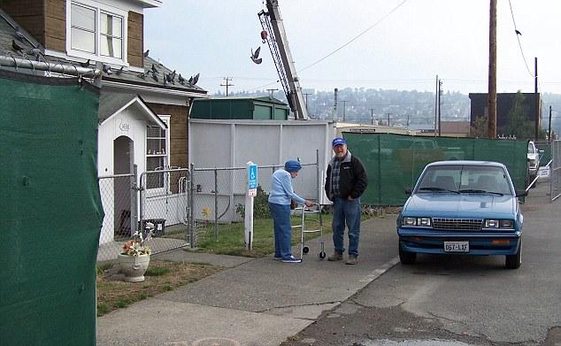 mujer y hombre frente de una casa