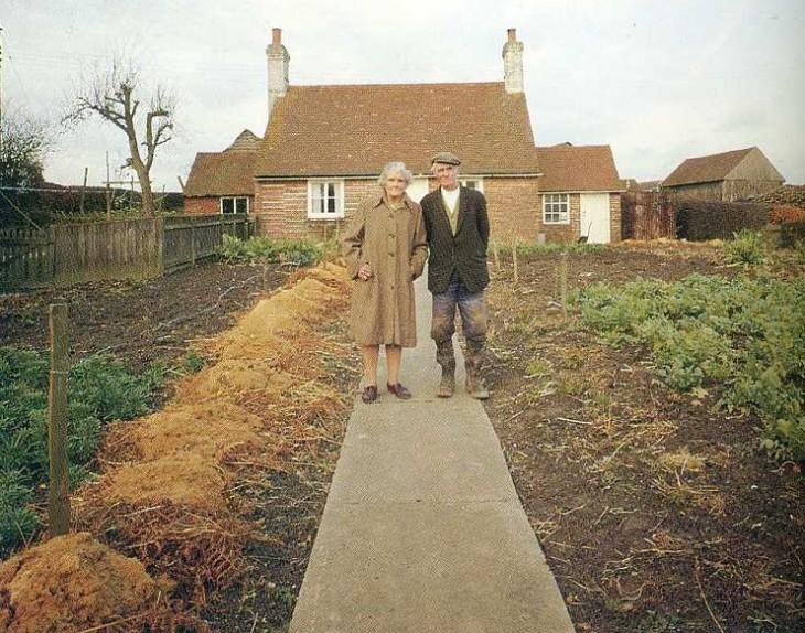 hombre y mujer al frente de su casa otono