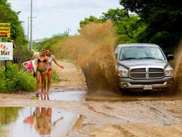 pareja pidiendo aventon y mojados por auto