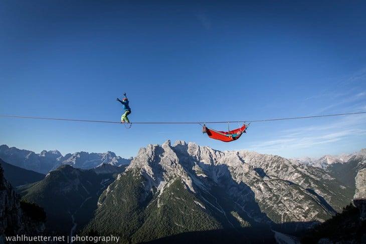 hombre haciendo equilibrio en una soga en los alpe