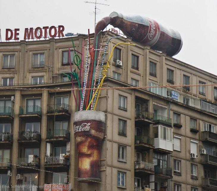 botella de coca cola derramandose sobre un edificio