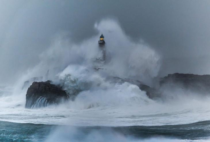 una ola gigante choca contra un faro