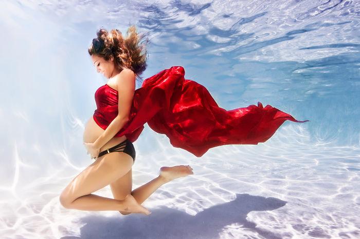 mujer embarazada bajo el agua vestida de rojo