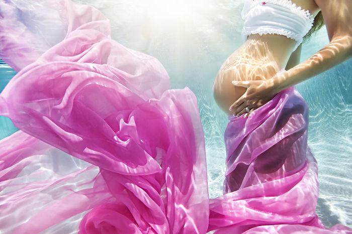 mujer embarazada bajo el agua vestida de blanco y violeta