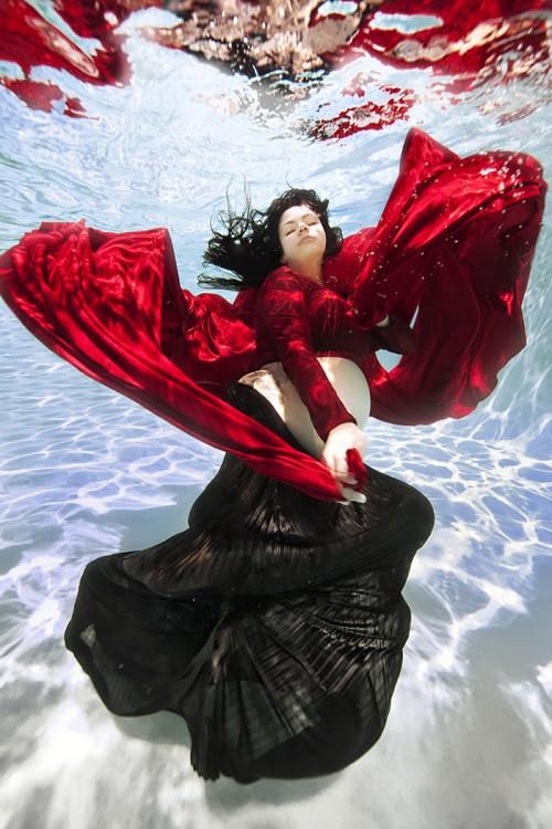 mujer embarazada bajo el agua vestida de rojo y negro
