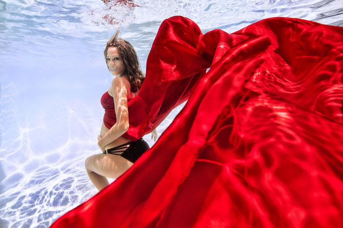 mujer embarazada bajo el agua vestido de rojo