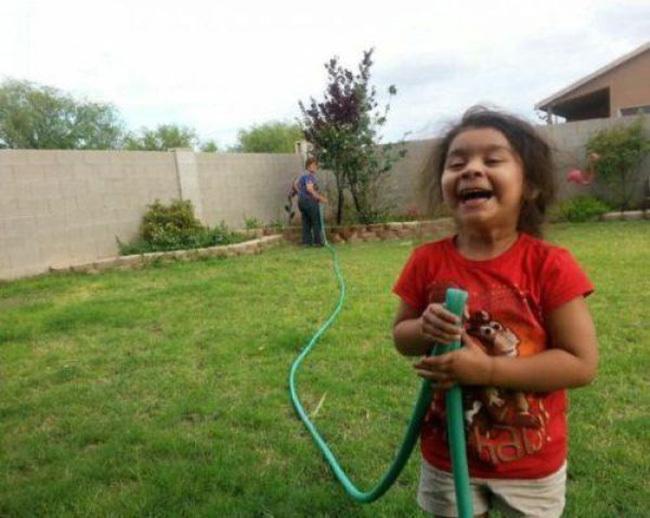 niña traviesa agarrando manguera