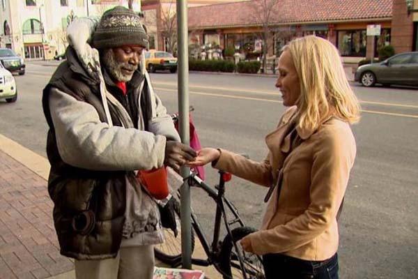 mujer dando donativo a persona pobre