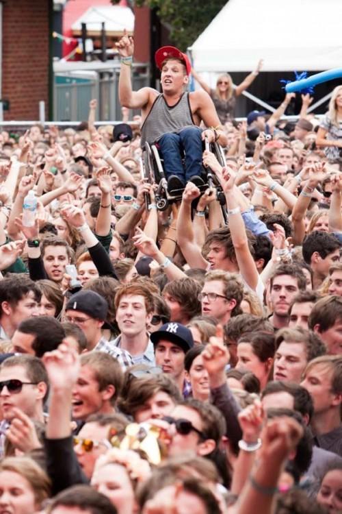 publico levantando a joven en silla de ruedas
