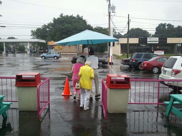 persona cubriendo de lluvia a ancianas